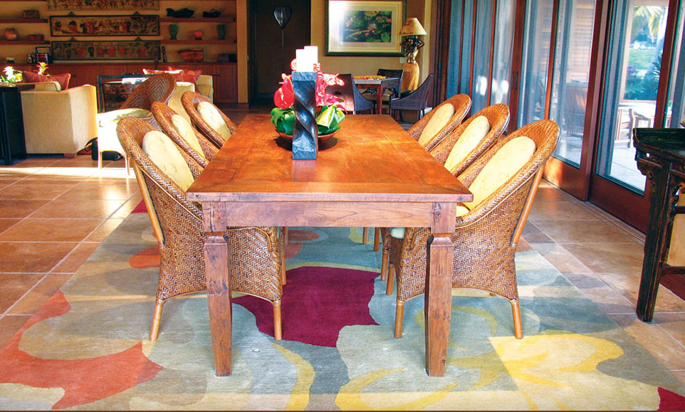 """The dining area of the home of John and Arlene Saffro at Four Seasons Hualalai Resort features a wool rug with the contemporary Hawaiian design called """"Kula Bloom,"""" with a hibiscus theme."""