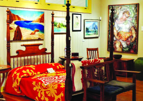 A solid koa four-poster bed, displayed with Hawaiian quilts, wood and resin art. photo by Catherine Tarleton
