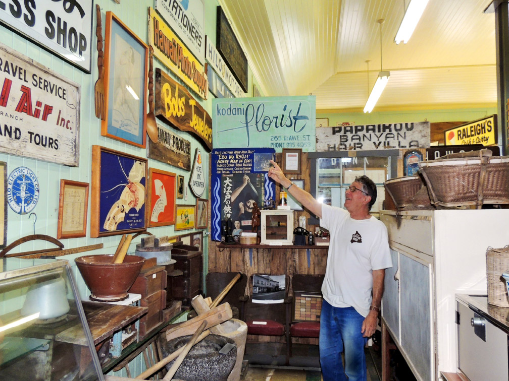 Glenn Carvalho, a volunteer at the Hawai'i Plantation Museum, points out signs of interest in their collection. photo by Catherine Tarleton