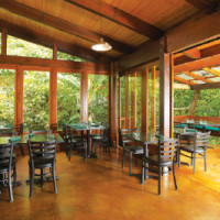 """The large """"windows"""" are doors repurposed from a Waiki'i Ranch remodel. The lānai bench is made of recycled wood, as are the roof beams and rafter support beams."""