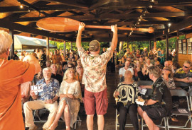 A carved paddle is featured at the 2015 auction with auctioneer Dick Herschberger. photo courtesy of Hawai'i Artist Collaboration