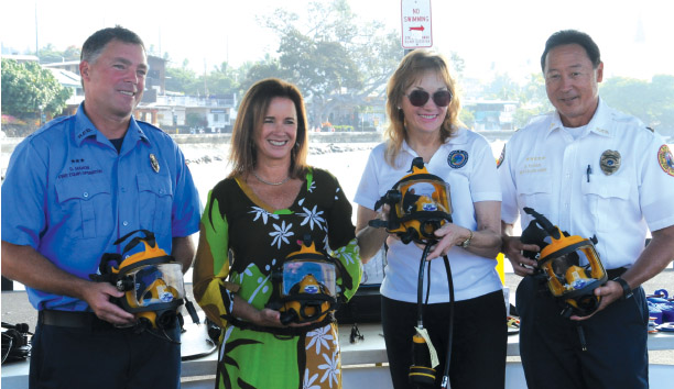 Ironman® Foundation provides a gift for underwater communication system for rescue divers. Captain David Mahon, Diana Bertsch -Vice President of Ironman®, Laura Sayre, and Battalion Chief Gerald Kosaki. photo courtesy of Laura and Frank Sayre