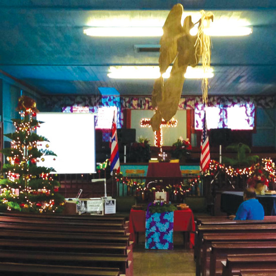 """The sanctuary decorated by the Kaiawe 'ohana for the Christmas season, featuring Christmas trees, wreaths, garlands, lights, and golden angels """"flying"""" from the ceiling. (Photo by Glenn Kaiawe) photo courtesy of Puka'ana Church"""