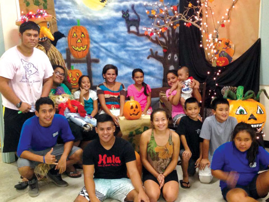 Puka'ana Church youth pose with the church's fall and Halloween display at a community pumpkin carving event in October, 2015. (photo by Glenn Kaiawe) photo courtesy of Puka'ana Church