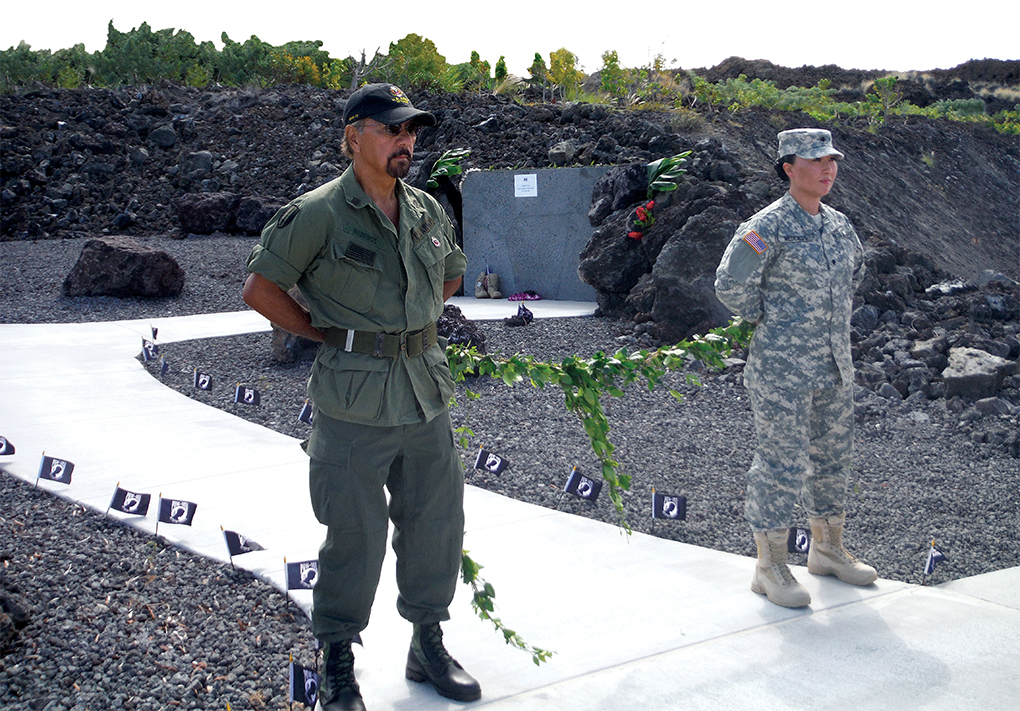 Father Clarence and daughter Kareen as human stanchions to hold the lei in the untying ceremony at the 2014 POW-MIA Memorial Garden blessing at the West Hawaii Veterans Cemetery.