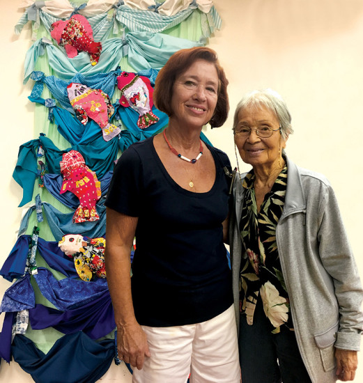 Before an aquatic-themed wall tapestry, Lori Thal and HIAC founder Betty Nagao share time at HIAC's Halloween party. photo by Paula Thomas
