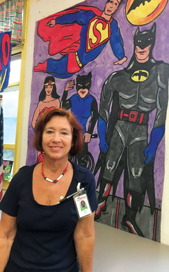 Lori stands in front of the Superhero banner painted by participants for the HIAC celebration of Halloween. photo courtesy of HIAC