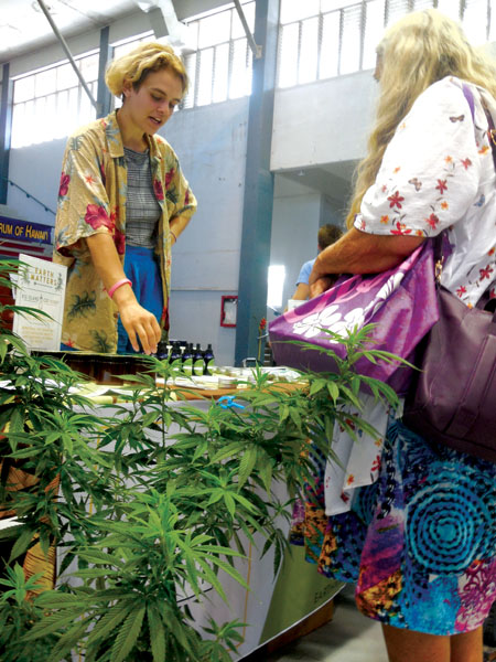 Vendors at the Hawai'i Cannabis Awareness Conference, held inside Hilo's Afook-Chinen Civic Auditorium in mid-June, display their wares and help answer customer questions about CBD and other hemp products. photo by Stefan Verbano