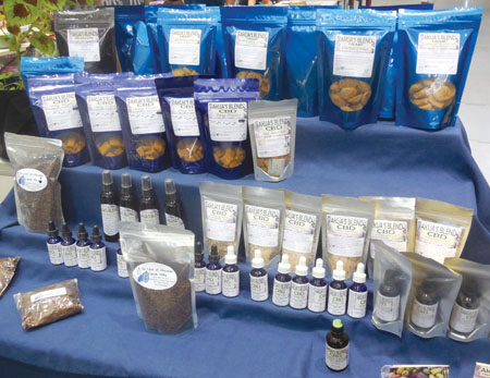 Vendors at the Hawai'i Cannabis Awareness Conference, held inside Hilo's Afook-Chinen Civic Auditorium in mid-June, offer everything from CBD cookies and snacks to cosmetics, chocolates, and oils–even dog treats! photo by Stefan Verbano